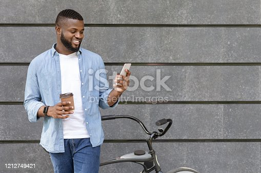 istock Black guy standing near bicycle, texting on smartphone and drinking coffee 1212749421