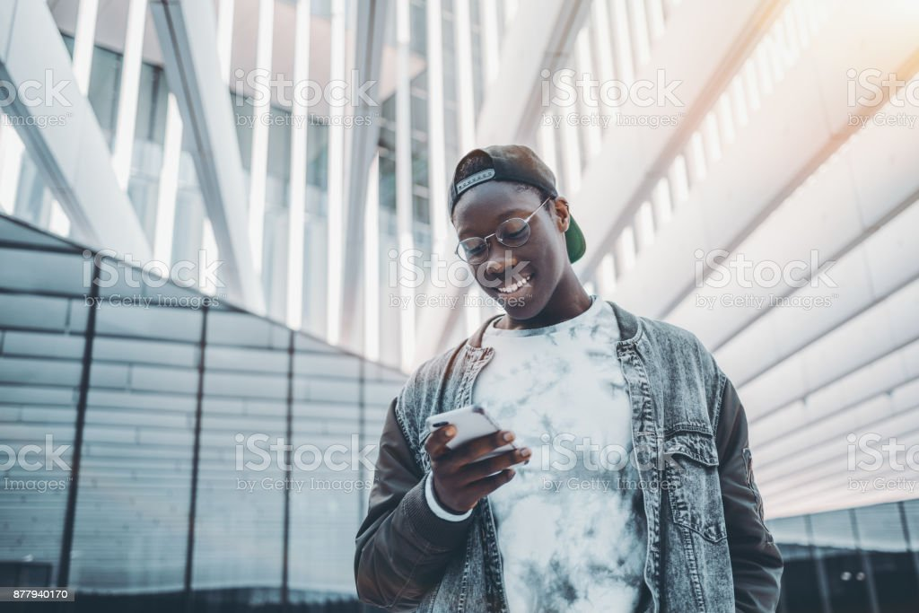 Black guy typing message on his cellphone stock photo
