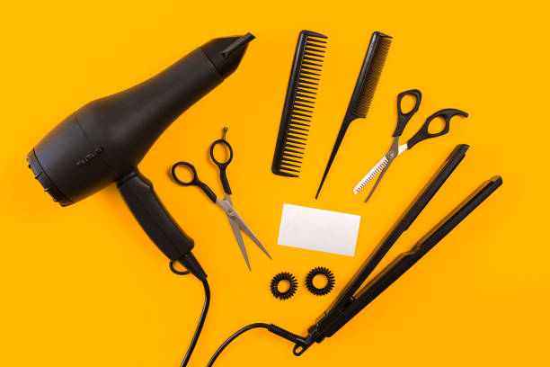 Black hair dryer, comb and scissors on yellow paper background. Top view Black hair dryer, comb and scissors on yellow paper background. Top view. Copy space. Still life. Mock-up. Flat lay overhead projector stock pictures, royalty-free photos & images