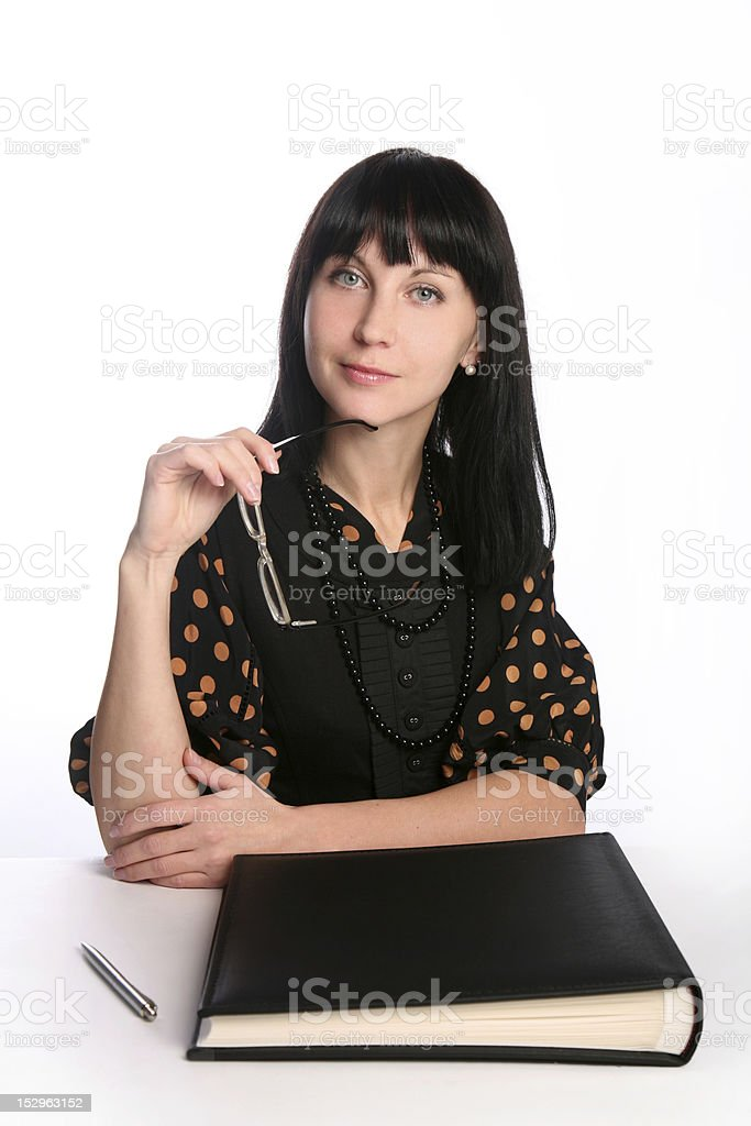 Black haired businesswoman sitting with album holding glasses royalty-free stock photo
