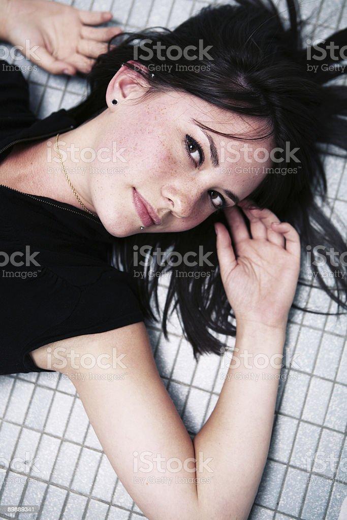 Black langhaarigem Mädchen Leg dich auf Fliesenboden. Lizenzfreies stock-foto