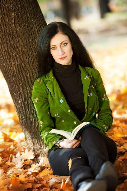 black langhaarigem mädchen liest ein buch im park - natürliche make up kurse stock-fotos und bilder
