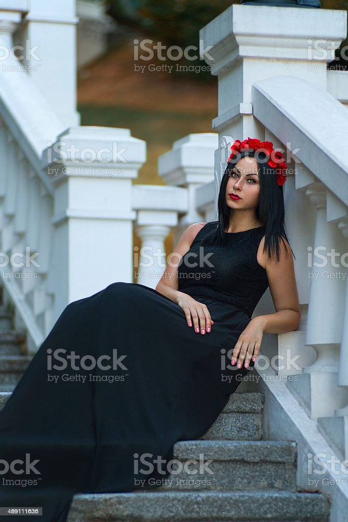 Black haired woman in the dark dress are waiting stock photo