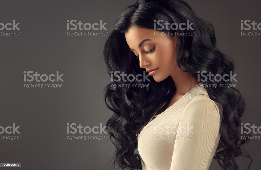Black haired woman with voluminous, shiny and curly hairstyle.Frizzy hair. stock photo
