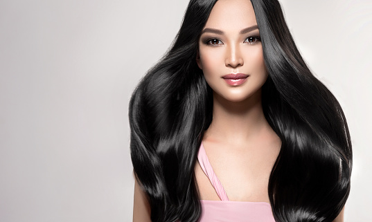 Black haired young woman with asian appearance is demonstrating dense, well cared, straight hair and vivid evening makeup on the face.Asian beauty. Hairdressing art, hair care and beauty products.