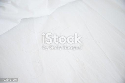 istock black hairs on white mattress near white pillow, Concept : hair fall problem 1039491204