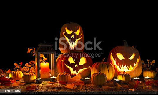 Background with carved scary pumpkins, candles and dry leaves on a wooden base