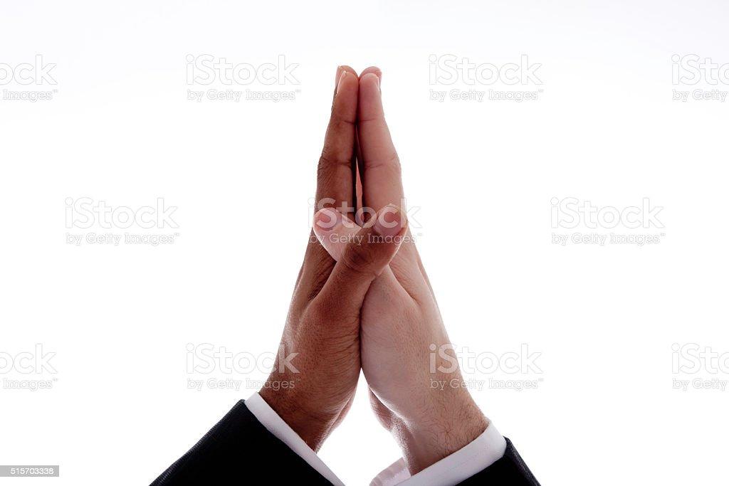 Black hand, white hand, folded in prayer stock photo
