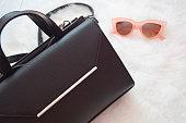 黒のハンドバッグと白地にピンクのメガネ。ファッションの概念。トップ ビュー