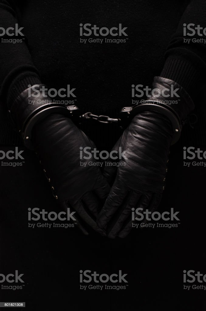 Black handcuffs leather black gloves, concept Black handcuffs leather black gloves, concept Arrest Stock Photo