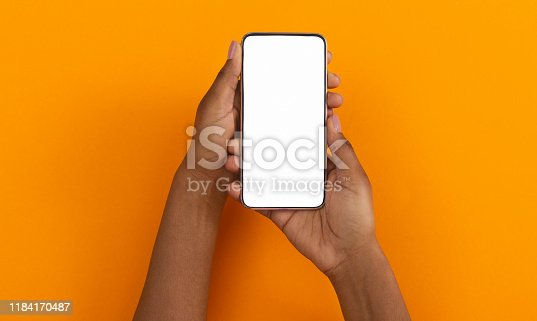 istock Black hands holding smartphone with blank screen for mockup 1184170487