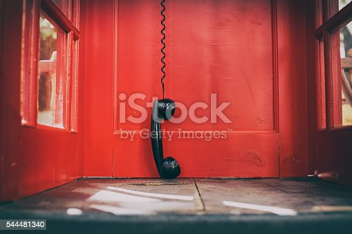 telephone receiver hanging touching the floor in a red call telephone booth. the concept of technological progress and the development of communication. Hanging up