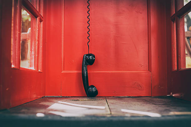 black handset hanging in a red telephone box foto