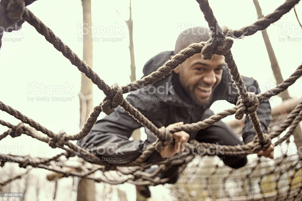 Black handsome young man climbing over obstacle during mud run stock photo