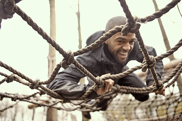 Black handsome young man climbing over obstacle during mud run Black handsome young man climbing over obstacle during mud run obstacle course stock pictures, royalty-free photos & images