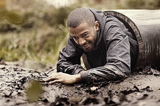 black handsome young man crawling through obstacle during mud run - kruipruimte stockfoto's en -beelden
