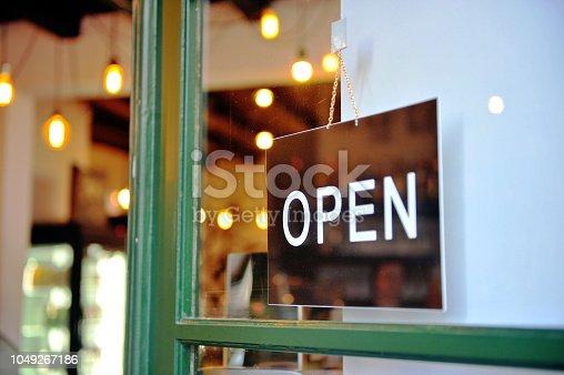 Black hanging open sign in the green wooden door of retail store, business background