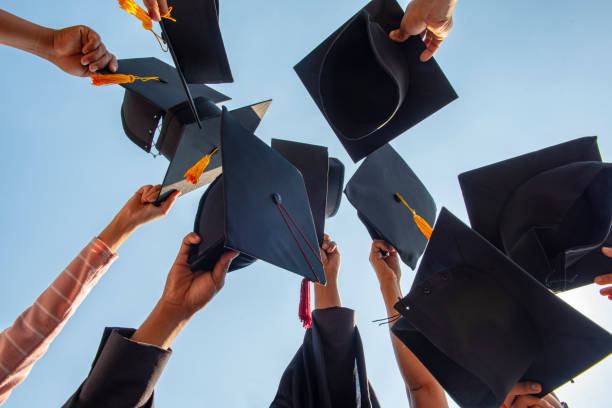 black hat of the graduates floating in the sky. - graduation cap stock pictures, royalty-free photos & images