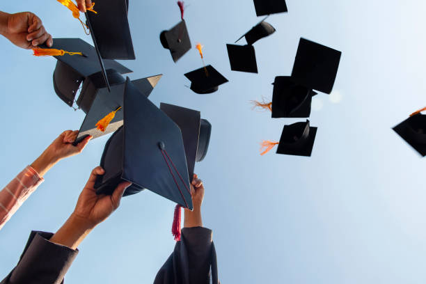 Black hat of the graduates floating in the sky. Black hat of the graduates floating in the sky. alumnus stock pictures, royalty-free photos & images