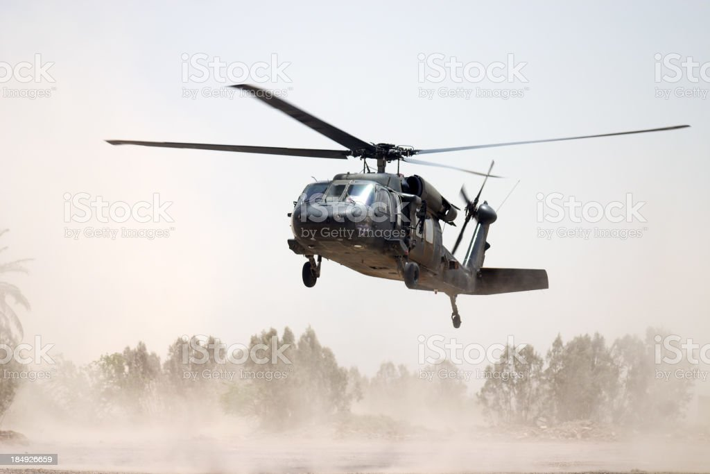Black Hawk helicopter hovering above a dusty ground stock photo