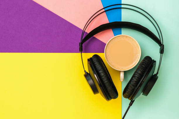 Black headphones and a Cup of coffee on a colorful background. The view from the top. stock photo