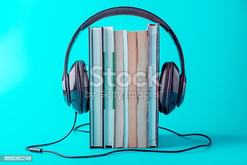 istock Black headphones with a stack of books on a blue background. Concept of audiobooks and modern education 899060248