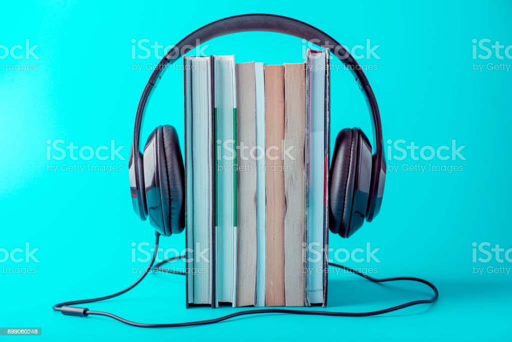 Black headphones with a stack of books on a blue background. Concept of audiobooks and modern education stock photo