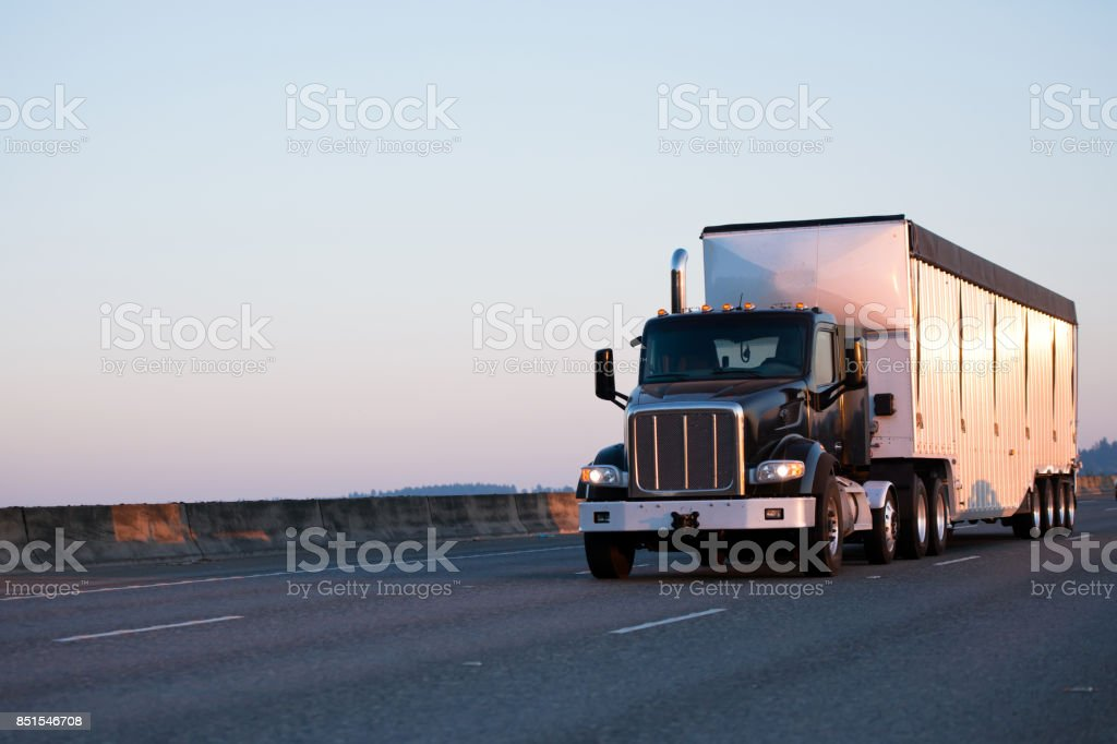 Black heavy class big rig semi truck with day cab for local deliveries transport bulk semi trailer with grooved walls on the roadway stock photo