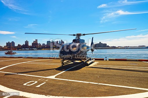 Black Helicopter on helipad in Lower Manhattan New York, USA, on East River. Pier 6. East River and skyscrapers on the background