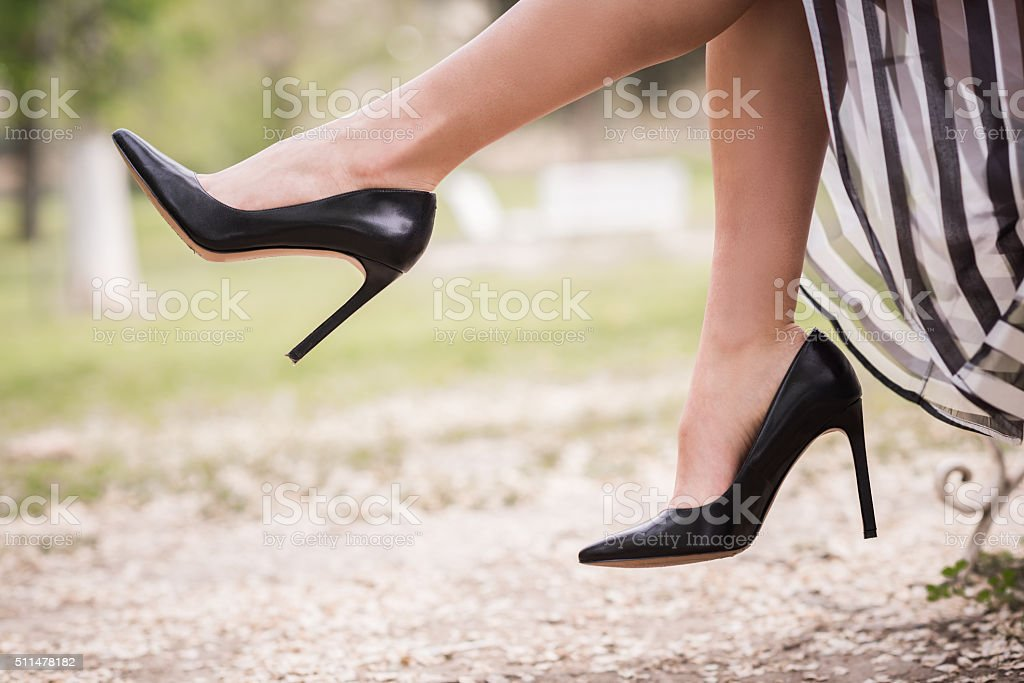 Black high heels on the feet of a young woman stock photo