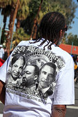 Palm Springs,United States- February 23,2013: Afro American male wearing Black History T Shirt at the Black History Parade Palm Springs California. The back of the T Shirt says, 'God Bless America. Rosa sat so Martin could walk. Martin walked so Obama could run. Obama ran so our children can fly.' Photographs of Rosa Parks,Martin Luther King and Barack Obama are silk screened on the back. The statue of Liberty is in the background.  Black History Month is an annual event every February.