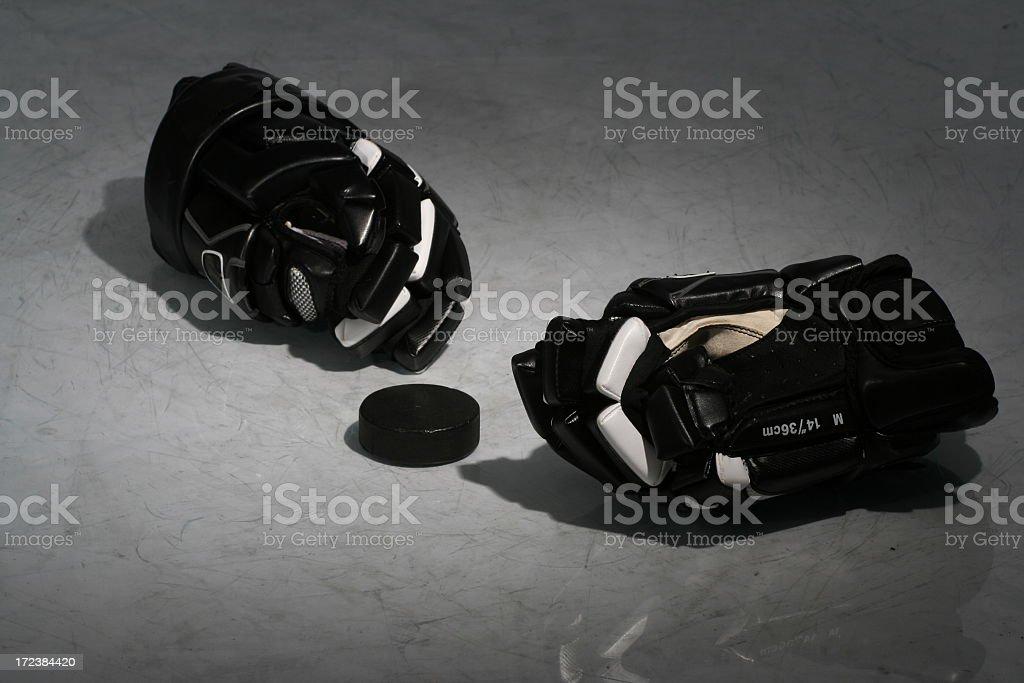 Black hockey equipment laying on an ice rink stock photo