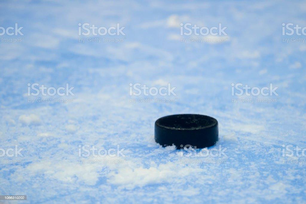 black hockey puck on ice rink. Winter sport.