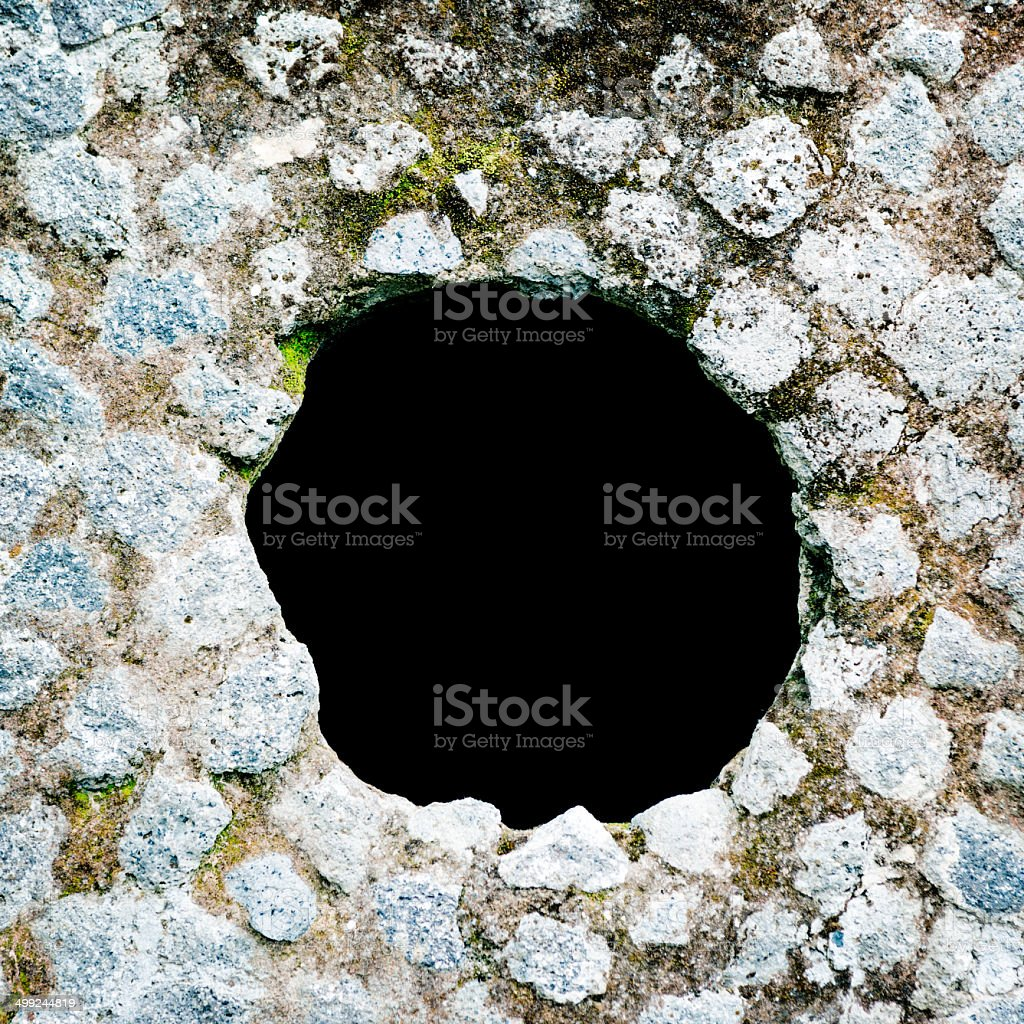 Ancient, stone wall with hole. Photo taken in ancient ruins of...