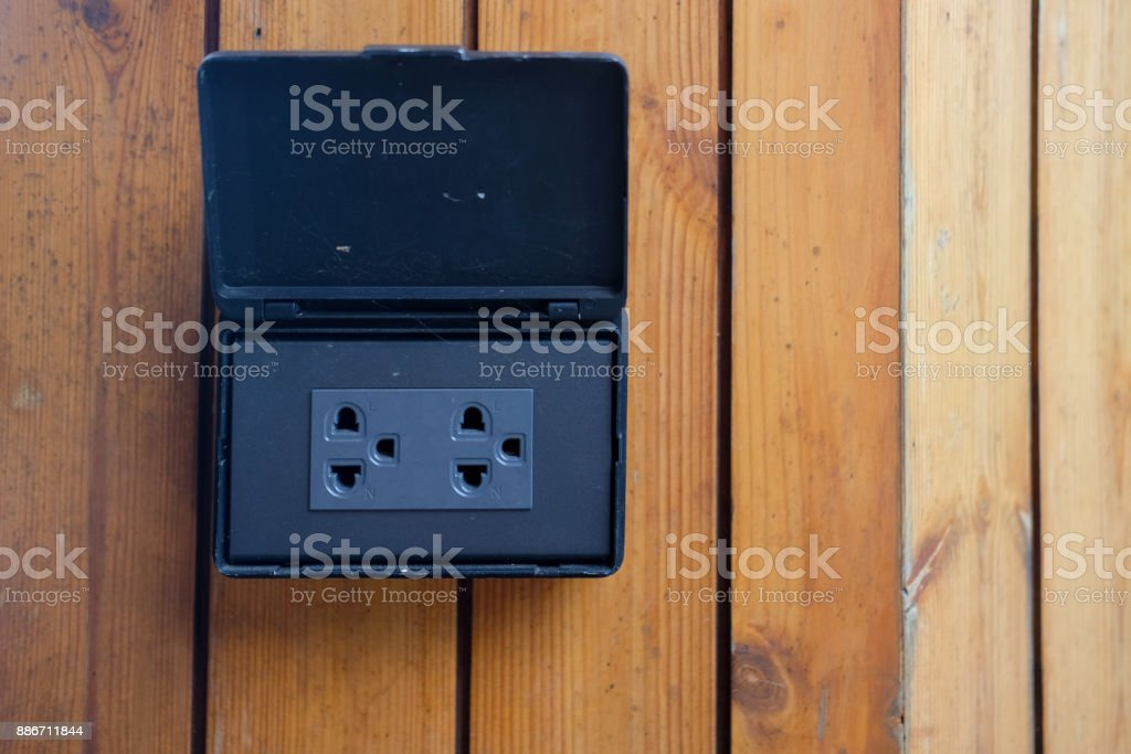 Black home electrical outlet on a light wood wall. stock photo