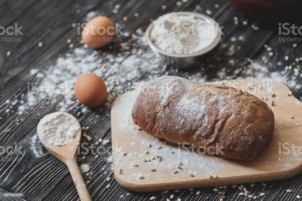 Black homemade bread and its ingredients on black rustic table stock photo