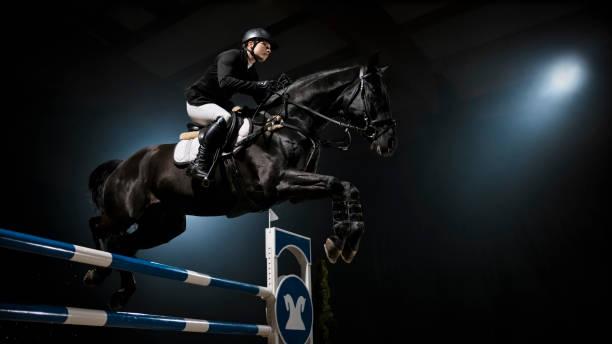 Cheval noir sauter rail avec son cavalier - Photo