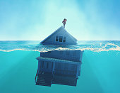 House sinking into the ocean . Half splitted image in the sea of a home floating . Debt and bankruptcy concept . This is a 3d render illustration .