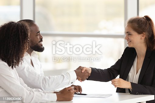 istock Black hr manager handshake with young female applicant starting interview 1139630490