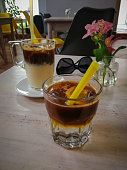 black iced coffee with milk and with tonic water on a wooden table