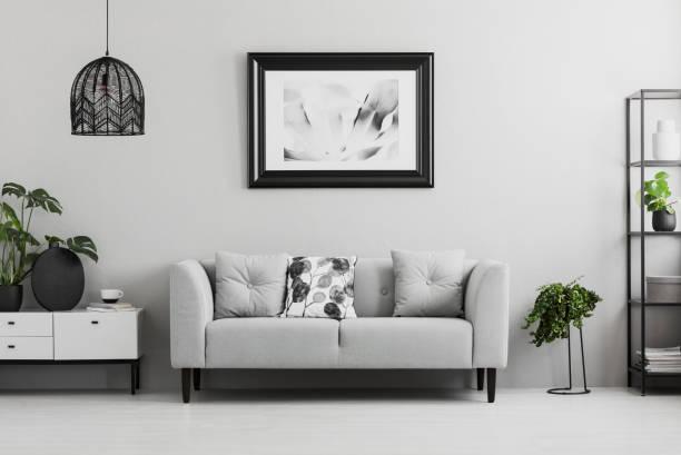 schwarzen industrielle bücherregal und eine pflanze stehen neben ein gepolstertes sofa in einem grauen wohnzimmer interieur mit platz für einen couchtisch. echtes foto - anrichte weiß stock-fotos und bilder