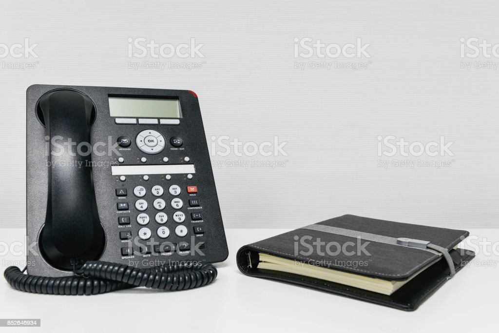 Black IP Phone and notebook on the white table stock photo