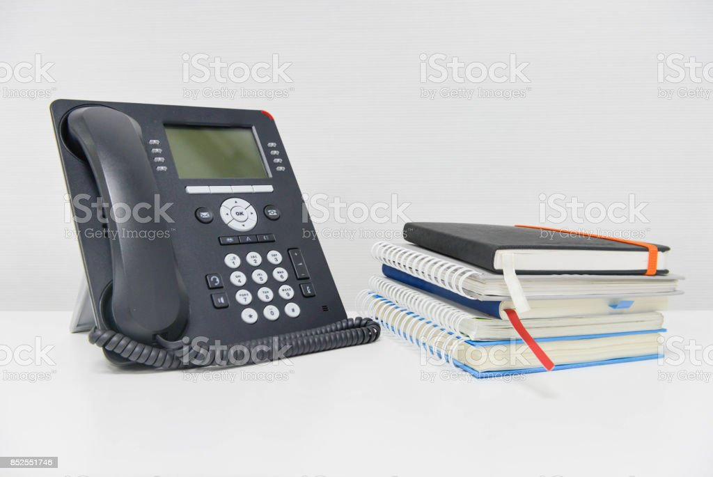 Black IP Phone and stack of books stock photo