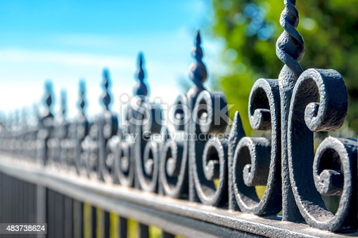 Horizontal composition photography of close-up in selective focus of iron fence, barrier, ornate with volute and curve. The black railing is taken in dimishing perspective on blurred blue sky and green tree background in sunny day of summer season.