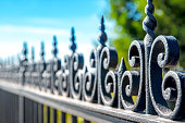 Black iron fence volute outdoor perspective in selective focus
