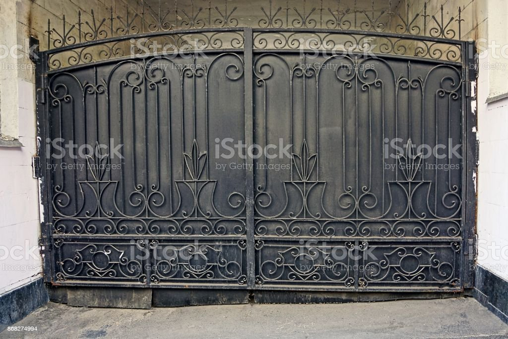 The large iron gate of black color on the city street
