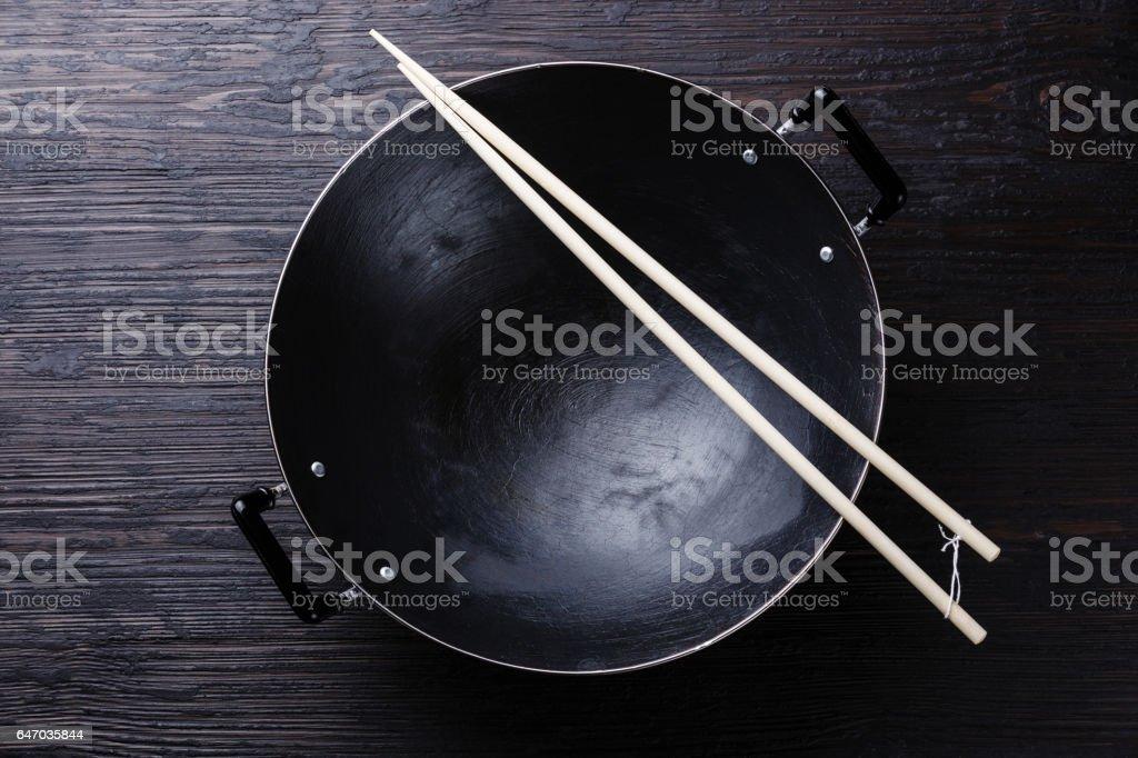 Black iron wok pan with Culinary long sticks stock photo