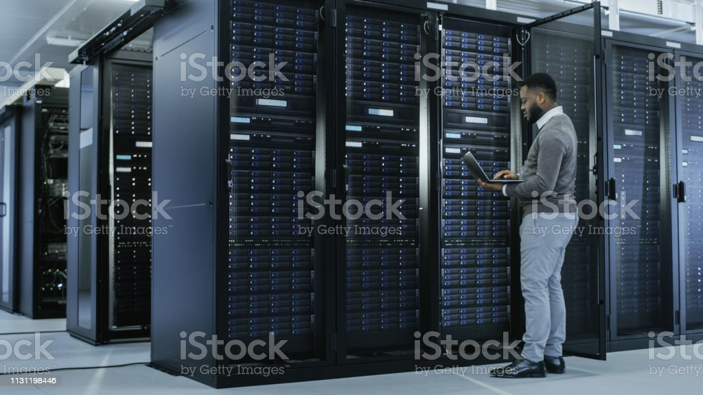 Black IT Specialist is Working on Laptop in Data Center while...
