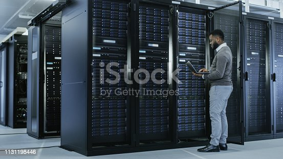 1131208605 istock photo Black IT Specialist is Working on Laptop in Data Center while Standing Before Server Rack. Running Diagnostics, Putting in Data or Doing Maintenance Work. 1131198446