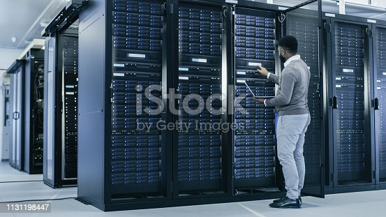 1131208605istockphoto Black IT Specialist is Working on Laptop in Data Center while Standing Before Server Rack. Running Diagnostics, Putting in Data or Doing Maintenance Work. 1131198447